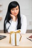 Mulher de negócio bonita nova que senta-se na mesa Fotografia de Stock Royalty Free