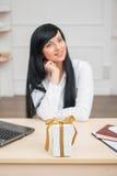 Mulher de negócio bonita nova que senta-se na mesa Fotos de Stock Royalty Free
