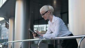 Mulher de negócio bonita nova que usa o PC da tabuleta fora do centro Fotografia de Stock
