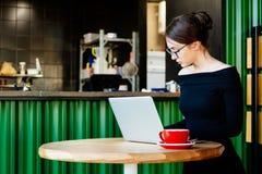 A mulher de negócio bonita nova trabalha em um portátil imagem de stock