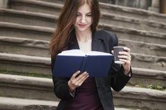 Mulher de negócio bonita que aprecia em uma xícara de café e em um livro imagem de stock