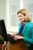 Mulher de negócio bonita que datilografa e que sorri Foto de Stock