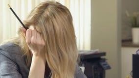 Mulher de negócio bonita que morde seu lápis no escritório video estoque