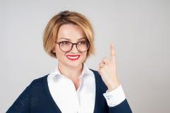 Mulher de negócio bonita que mostra o dedo acima e a vista de sorriso acima Fotos de Stock