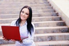 Mulher de negócio bonita que senta-se em escadas com portátil imagem de stock
