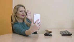 Mulher de negócio bonita que sorri e que levanta para a foto do selfie no telefone celular filme