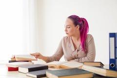 Mulher de negócio bonita que trabalha em um escritório atrás de uma tabela com livros imagens de stock