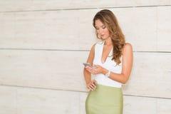 A mulher de negócio bonito usa seu telefone no escritório Imagens de Stock