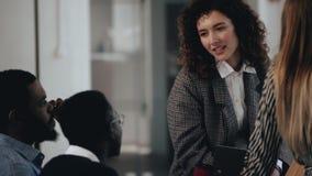 Mulher de negócio caucasiano atrativa nova feliz que fala a dois colegas masculinos pretos na tabela moderna do escritório do sót vídeos de arquivo