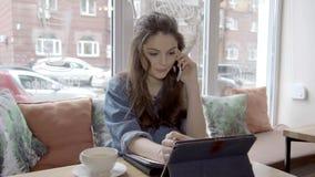 A mulher de negócio caucasiano nova fala o telefone e surfar em uma tabuleta no café filme