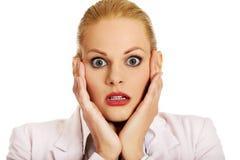 Mulher de negócio chocada que guarda as mãos no queixo fotografia de stock royalty free