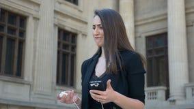 Mulher de negócio com a baixa bateria em seu smartphone que sente nervoso sobre não poder carregar video estoque