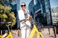 Mulher de negócio com a bicicleta no distrito financeiro fora imagens de stock royalty free