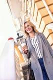 Mulher de negócio com café que sorri na rua imagem de stock royalty free