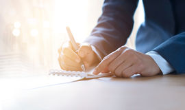 Mulher de negócio com escrita da pena no caderno na iluminação vibrante Fotografia de Stock Royalty Free