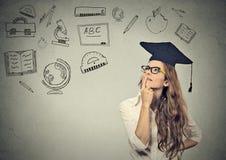 Mulher de negócio com o chapéu da graduação que olha acima de pensamento sobre a educação foto de stock royalty free
