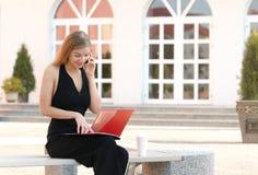 Mulher de negócio com o dobrador nas mãos que fala pelo telefone fotos de stock royalty free