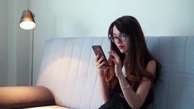 Mulher de negócio com o smartphone que senta-se no sofá em casa video estoque