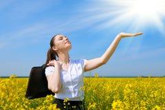 Mulher de negócio com a pasta que relaxa no sol inferior exterior do campo de flor Moça no campo amarelo da colza La bonito da mo Imagens de Stock