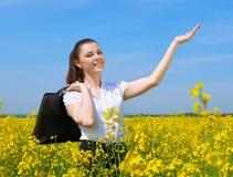 Mulher de negócio com a pasta que relaxa no sol inferior exterior do campo de flor Moça no campo amarelo da colza La bonito da mo Foto de Stock