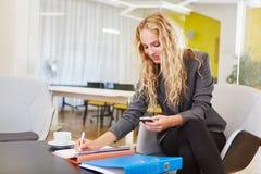 Mulher de negócio com planeamento do smartphone Imagem de Stock
