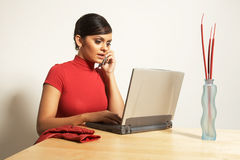 Mulher de negócio com portátil e telefone Fotografia de Stock Royalty Free
