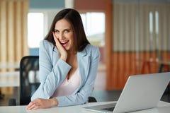 A mulher de negócio comemora algo em seu local de trabalho Imagens de Stock Royalty Free