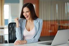 A mulher de negócio comemora algo em seu local de trabalho Fotos de Stock