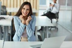 A mulher de negócio comemora algo em seu local de trabalho fotos de stock royalty free