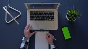 A mulher de negócio considera a renda usando um portátil e um caderno ao lado do telefone Tiro aéreo video estoque