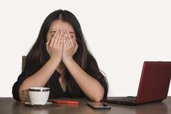 Mulher de negócio coreana asiática deprimida que trabalha no esforço na mesa do computador de escritório que sente a dor de cabeç fotografia de stock