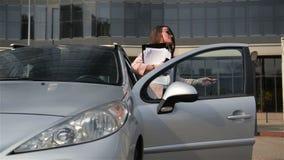 A mulher de negócio da forma com papéis financeiros sai de seu carro A senhora Is Holding Important documenta para o trabalho dur video estoque
