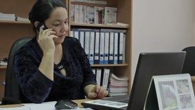 Mulher de negócio da Idade Média que fala no telefone celular no escritório Retrato da mulher de negócio de sorriso filme