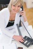 Mulher de negócio da Idade Média que faz o atendimento de telefone Imagem de Stock Royalty Free