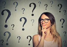 Mulher de negócio de pensamento com os vidros que olham acima na marca de muitas perguntas Fotografia de Stock Royalty Free