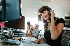 Mulher de negócio de sorriso com os auriculares que trabalham em sua mesa Fotografia de Stock Royalty Free