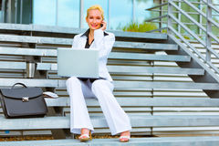 Mulher de negócio de sorriso com portátil que fala no phon Fotografia de Stock Royalty Free