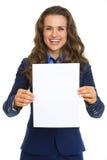 Mulher de negócio de sorriso que mostra a folha do papel vazio Imagens de Stock Royalty Free