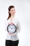 A mulher de negócio de sorriso que realiza nas mãos cronometra, isolado no branco Imagens de Stock Royalty Free