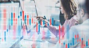 Mulher de negócio e seu colega que sentam o laptop dianteiro com gráficos e estatísticas financeiros no monitor dobro fotos de stock