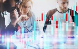 Mulher de negócio e seus colegas que sentam o laptop dianteiro com gráficos e estatísticas financeiros no monitor dobro imagem de stock