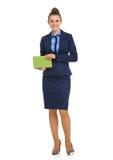 Mulher de negócio elegante que está e que guarda o caderno Fotografia de Stock