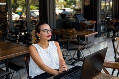 Mulher de negócio elegante que trabalha em linha em um café exterior imagem de stock royalty free