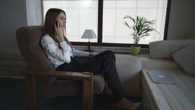 Mulher de negócio em casa que fala no telefone perto da janela filme