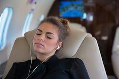 Mulher de negócio em um jato incorporado que relaxa e que escuta o musi Imagens de Stock Royalty Free