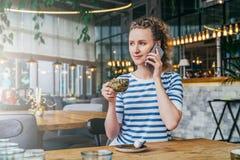 A mulher de negócio em um t-shirt listrado está sentando-se em uma tabela em um café, café bebendo e está falando-se no telefone  Imagem de Stock
