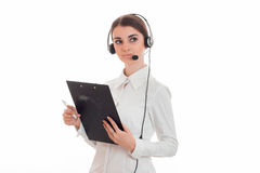 A mulher de negócio encantador nova no uniforme com fones de ouvido e o microfone que olha ausente e fazem as anotações isoladas  Imagens de Stock