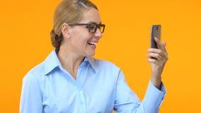 Mulher de negócio entusiasmado com o smartphone que mostra sim o sinal, sucesso novo do projeto filme