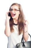Mulher de negócio entusiasmado que fala no smartphone foto de stock
