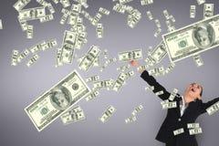 Mulher de negócio entusiasmado que olha a chuva do dinheiro contra o fundo roxo imagem de stock
